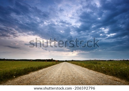 Evening country road with dramatic sky - stock photo