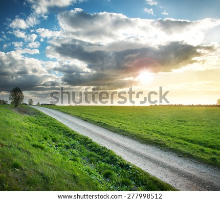 Evening country road with dramatic sky and green field
