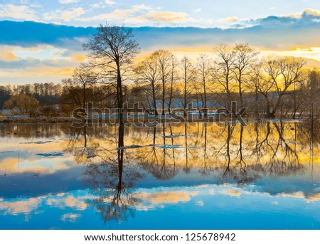 Evening dawn over spring flood of the river - stock photo