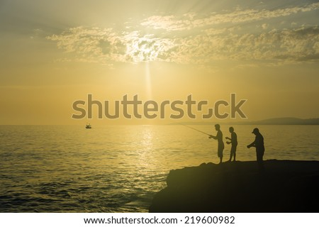 Evening fishing on the Mediterranean Sea. Turkey. Silhouette of fishermen. - stock photo