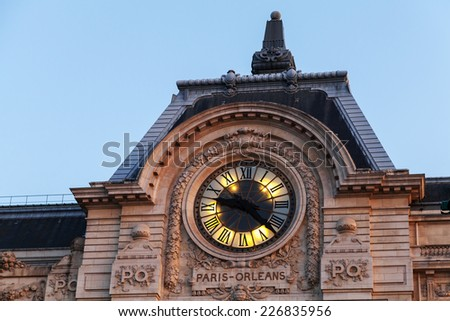 Evening illumination of famous ancient clock on the wall of Orsay Museum in Paris - stock photo