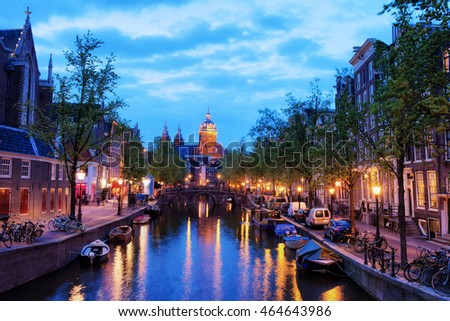 Evening in city of Amsterdam in Holland, The Netherlands, Oudezijds Voorburgwal canal, Church of St. Nicholas at the far end.