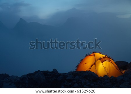 Evening in the Caucasus mountains and orange tent on a stones - stock photo