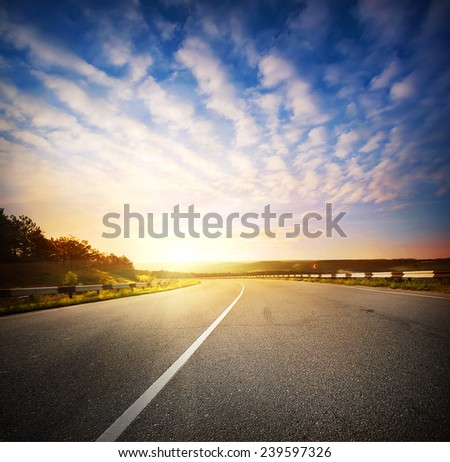 Evening landscape with a road going into the horizon at sunset sky - stock photo