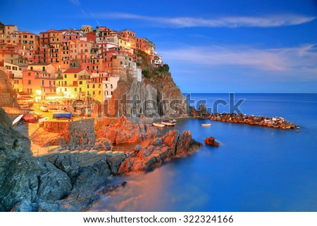 Evening lights lit the village of Manarola above the sea, Cinque Terre, Italy - stock photo