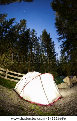 Evening lit tent in camping. Dolomities, Italian Alps, Europe. Concept: nature, vacation, outdoor - stock photo