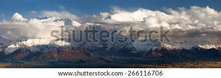 "Evening panoramic view of Lenin Peak from Alay range - Kyrgyz Pamir Mountains - Kyrgyzstan and Tajikistan border- Central Asia ""Roof of the World"" - stock photo"