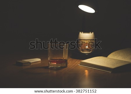 Evening reading a book. Glass of whiskey, cigarettes and a box of matches, a candle in the aroma lamp - stock photo