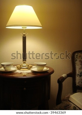 Evening rest. Two cups on the table & open book on the armchair - stock photo