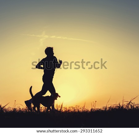 Evening runner with dog - stock photo
