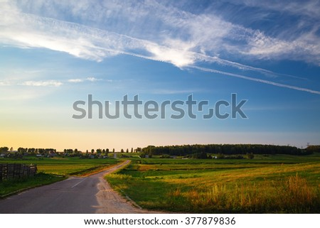 Evening rural landscape with road, field grass and beautiful blue sky. - stock photo