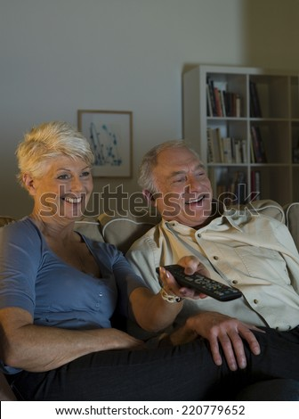 Evening scene of a happy elderly couple watching television in their living room - stock photo
