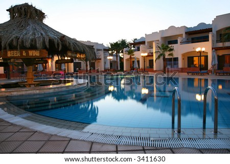 Evening shot of swimming pool in tropical hotel