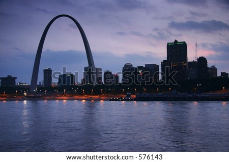 Evening shot of the St. Louis Gateway Arch in MO from across the Mississippi, in IL.  The view is over the river, and gives a nice skyline of St. Louis. - stock photo