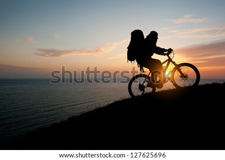 evening silhouette of a man climbing a mountain tourist on a bike - stock photo
