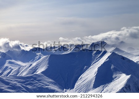 Evening snowy mountains in mist. Caucasus Mountains, Georgia, view from ski resort Gudauri. - stock photo