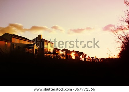 Evening sun setting on a row of suburban houses in a subdivision - stock photo