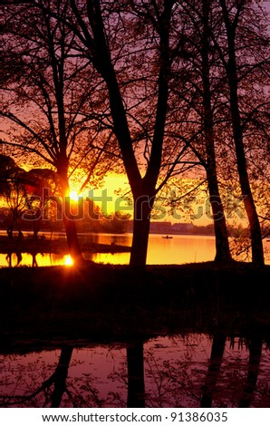 Evening sunset reflections on the lake in spring. Transparent water. Wonderful view. - stock photo