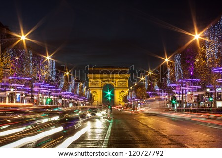 Evening traffic on Champs-Elysees in front of Arc de Triomphe (Paris, France) at Christmas Time - stock photo