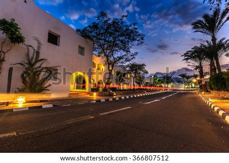 Evening view for road in illumination, white apartments, palm trees  - stock photo