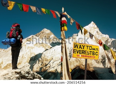 evening view of Everest with tourist and buddhist prayer flags from Kala Patthar, signpost and blue sky - way to Everest Base Camp - Nepal  - stock photo