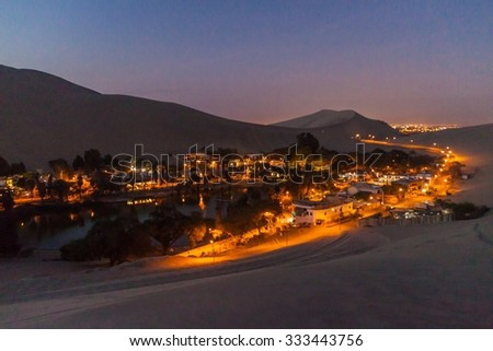 Evening view of illuminated desert oasis Huacachina near Ica, Peru - stock photo