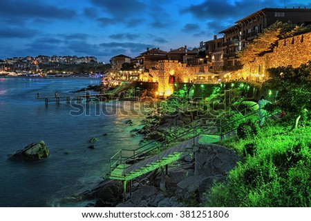 Evening view of Old Town of Sozopol (former ancient town of Apollonia) with Southern Fortress Wall and Tower in the yellow-green illumination, Bulgaria - stock photo