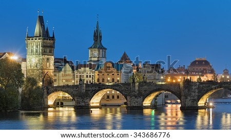 Evening view of the Charles Bridge in Prague, Czech Republic, with Old Town Bridge Tower, Old Town Water Tower and dome of the National Theatre - stock photo