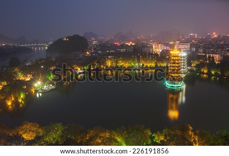 Evening view of the Gold and Silver Pagodas, also known as the Sun and Moon Pagodas, reflected in Shan Lake  Guilin, Guangxi Province, China. - stock photo
