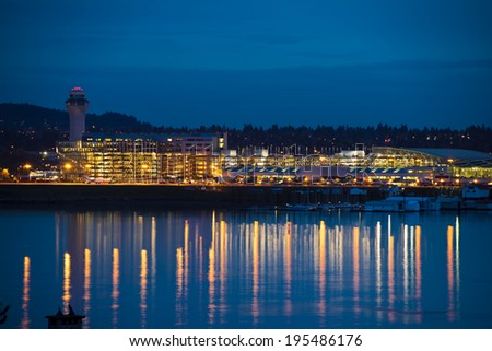 Evening view of the Portland airport with control tower, lights and reflection in the river, where boats are parked. In the lights parking of cars, aircraft, maintenance cars and trucks. - stock photo