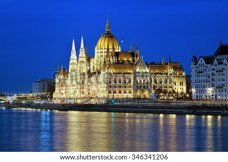 Eveninig view of the Hungarian Parliament Building in bright yellow illumination. View from the bank of Danube in Budapest, Hungary. - stock photo