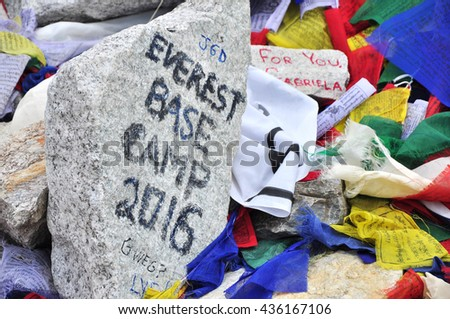 EVEREST BASE CAMP, NEPAL - CIRCA APRIL 2016: Everest Base Camp sign with stones, buddhist prayer flags and tents of climbers from everest expeditions.  - stock photo