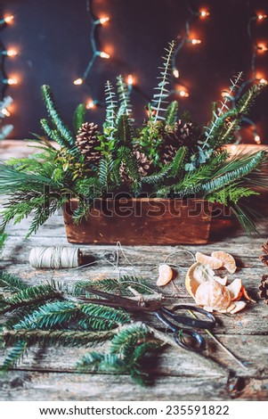 Evergreen Christmas centerpiece in the making on a wooden background with lights  - stock photo