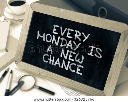 Every Monday is a New Chance. Inspirational Quote Handwritten on Chalkboard. Composition with Small Chalkboard on Working Table with Ring Binders, Office Supplies, Reports. Blurred, Toned Image.