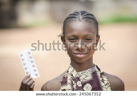 Everybody Against Diseases for Africa: Young Girl Showing Healing Pills - stock photo