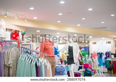 Everyday dressed woman mannequins and hangers with blouses in store - stock photo
