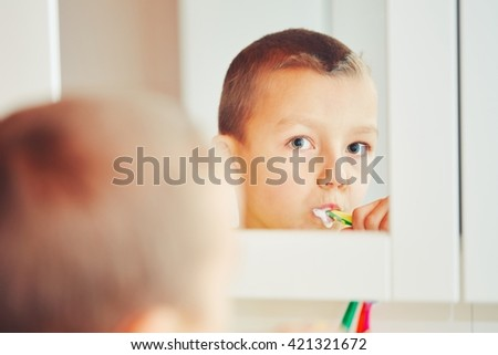 Everyday life at home. Little boy is cleaning teeth in the bathroom. - selective focus - stock photo