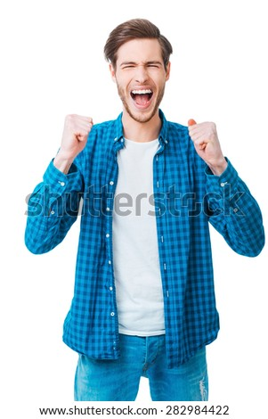 Everyday winner. Cheerful young man keeping arms raised and expressing positivity while standing against white background - stock photo
