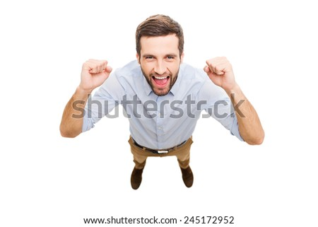 Everyday winner. Top view of happy young man expressing positivity and gesturing while standing isolated on white background - stock photo