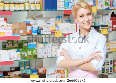 Everything for the best therapy. Young smiling druggist in white uniform standing with her arms crossed near the show case of a drug store