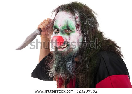 evil and scary clown holding a knife, isolated on white, concept horror and murderer - stock photo