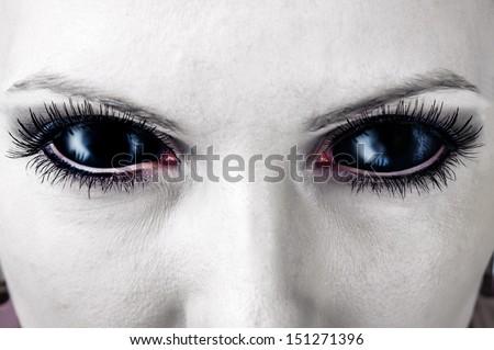 Evil black female alien, vampire or zombie eyes. dirt make up. Macro. Halloween theme  - stock photo