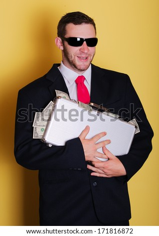 Evil business man hold suitcase with full of money notes - stock photo