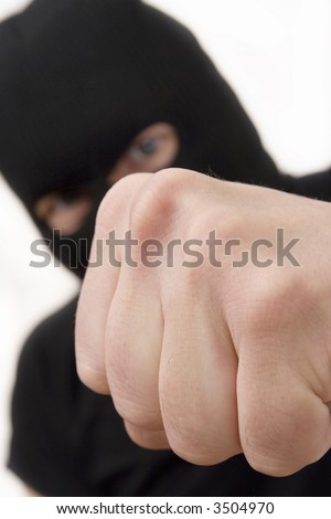evil criminal wearing military mask and throwing the fist - stock photo