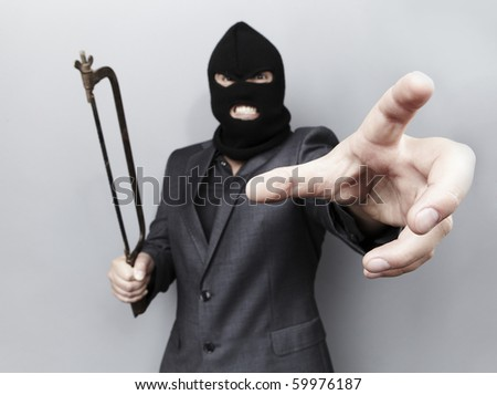 Evil criminal wearing military mask isolated on gray background.