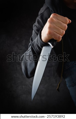 Evil criminal with large sharp knife ready for robbery or to commit a homicide - stock photo