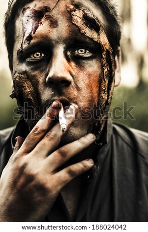 Evil dead zombie smoking cigarette with scary horror expression outdoors. Deadly habit - stock photo