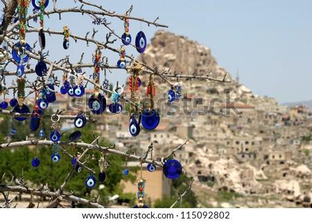 Evil eye in tree behind Uchisar Castle in Cappadocia, Nevsehir, Turkey. - stock photo
