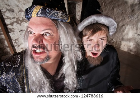 Evil long haired wizard with teenage son - stock photo