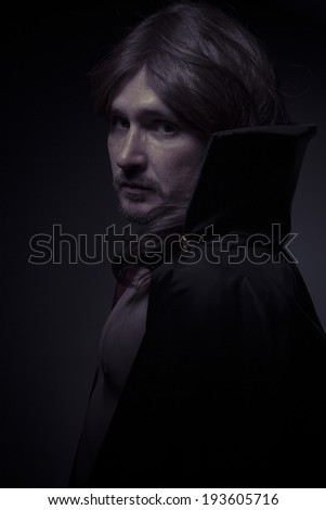 Evil man with long hair and black coat - stock photo